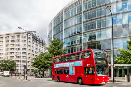 st pauls: LONDON, UK - AUGUST 21, 2015:  Cheapside street in London with a red bus and St. Pauls Cathedral reflected on a modern glass facade.