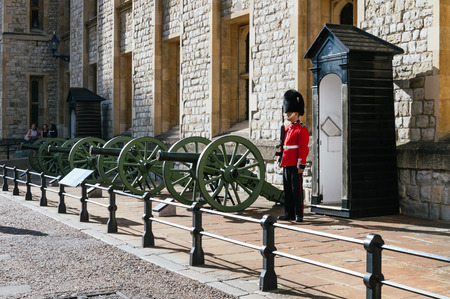 beefeater: LONDON, UK - AUGUST 21, 2015:  Queens Guard and guns - Tower of London. The Queens Guard is the contingents of infantry and cavalry soldiers charged with guarding the official royal residences in the United Kingdom.