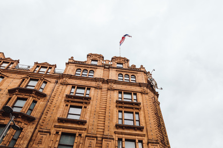 knightsbridge: London, UK - August 19, 2015: Low angle view of Harrods Department Store with a union jack flag on top. Harrods is the most famous and luxury department store in the world.