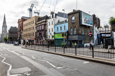 typically british: LONDON, UK - AUGUST 25, 2015: London street scene. Westminster Bridge Roadwith construction cranes ans retail stores on a overcast day Editorial