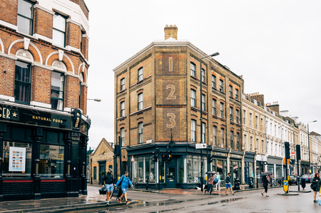 foodies: LONDON, UK - AUGUST 23, 2015: People crossing Bethnal Green Road a rainy day. It´s located in Shoreditch, near Brick Lane Market.