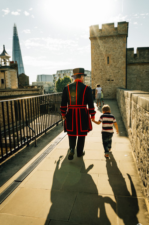 beefeater: LONDON, UK - AUGUST 21, 2015:  Yeoman warder and son in the Tower of London. The Yeomen Warders are popularly known as the Beefeaters and are ceremonial guardians of the Tower of London. Editorial