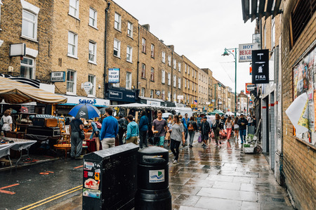 foodies: LONDON, UK - AUGUST 23, 2015: People at Brick Lane Market stalls a rainy day. Almost anything can be found on Brick Lane, from antique books to trendy and fashion designs.