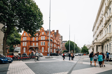 knightsbridge: London, UK - August 19, 2015: People walking on Exhibition Road in London. It is a street in South Kensington, London which is home to several major museums and academic establishments. Cloudy day.