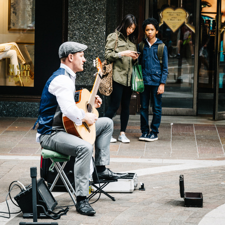 dozens: LONDON, UK - AUGUST 20, 2015: Street musician plays acoustic guitar near the entrance of Harrods while some people are listening. Dozens buskers perform on the streets of London. Editorial