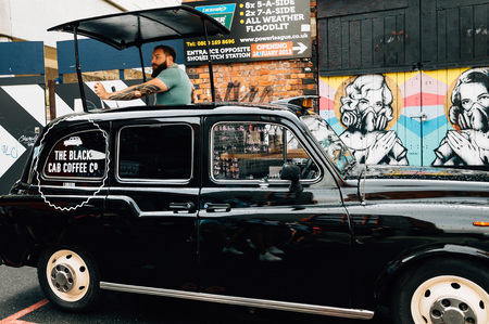 FOODIES: LONDON, UK - AUGUST 23, 2015: Man selling coffee inside a black cab on Brick Market. Brick Lane is famous for being a vibrant art and fashion area