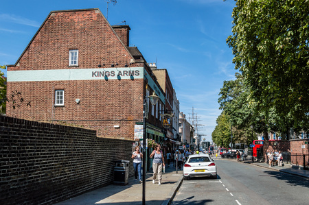 sark: LONDON, UK - AUGUST 22, 2015:  The streets of Greenwich with cutty sark on background a sunny day of summer with tourists walking on.