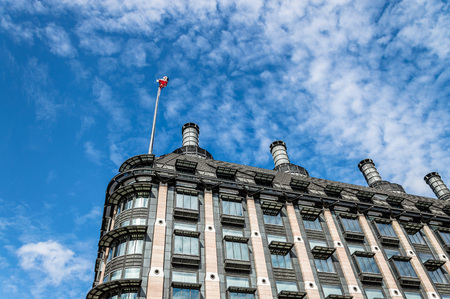 portcullis: London, UK - August 19, 2015: Low angle view of Portcullis House in London with the Union Jack flag against blue sky and white clouds, near Westminster Palace.