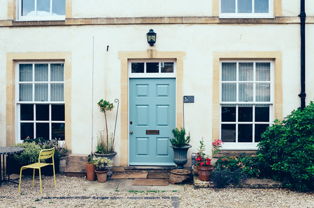 country house style: Cirencester, UK - August 18, 2015: English town house entrance with front courtyard and a painted closed door Editorial