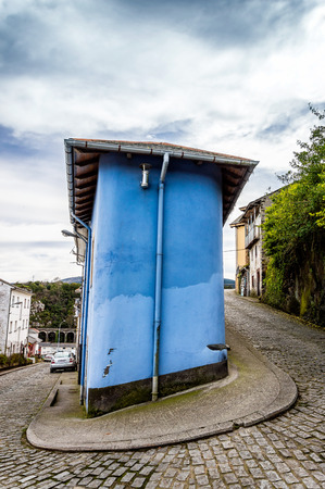 sloping: Blue house in an sloping paved street in the old town of Luarca on a cloudy day Stock Photo