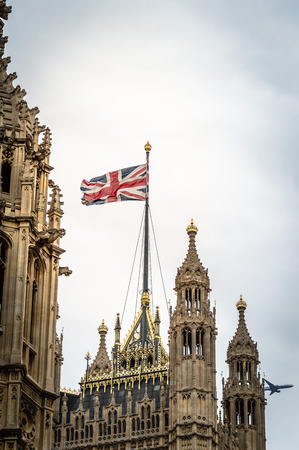 low angle view: Union Jack over Houses of Parliament, Westminster, London. Low angle view a cloudy day while an aircraft is on background