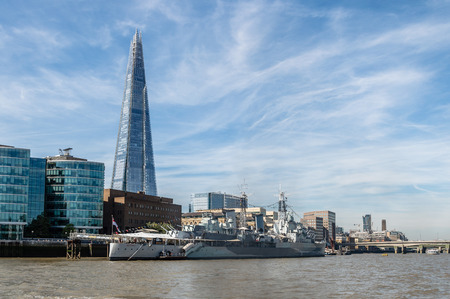 hms: London waterfront with HMS Belfast warship and office buildings a sunny day with blue sky