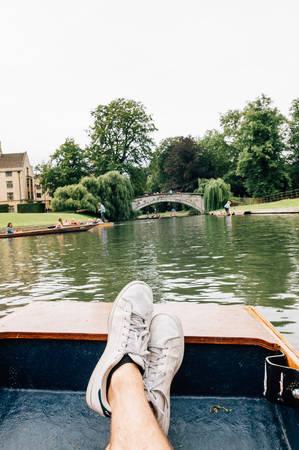 punting: Man feet on a boat punting in the river in  Cambridge. Focus on feet.