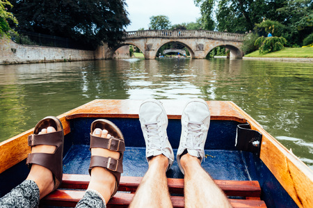 punting: Man and woman feet on a boat punting in the river in  Cambridge. Focus on feet.