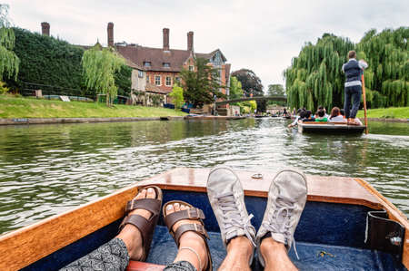 kingdom: Man and woman feet on a boat punting in the river in  Cambridge. Focus on feet.