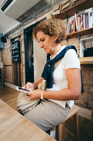 baby boomer: Woman sitting in a cafe with her smartphone. Casual clothes and curly hair. Stock Photo