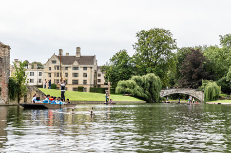 punter: CAMBRIDGE, UK - AUGUST 11, 2015:   Punting on the river Cam. Some companies and students hire punts to visitors and tourists. Cambridge is a university city and one of the top five universities in the world. Editorial
