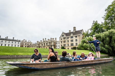 CAMBRIDGE, UK - AUGUST 11, 2015:   Punting on the river Cam. Some companies and students hire punts to visitors and tourists. Cambridge is a university city and one of the top five universities in the world. 新聞圖片