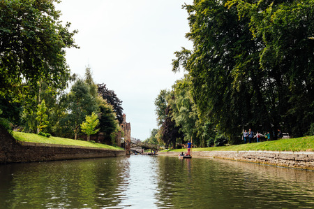 CAMBRIDGE, UK - AUGUST 11, 2015:   Punting on the river Cam. Some companies and students hire punts to visitors and tourists. Cambridge is a university city and one of the top five universities in the world. Editorial