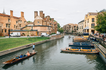 punting: CAMBRIDGE, UK - AUGUST 11, 2015:   Punting on the river Cam. Some companies and students hire punts to visitors and tourists. Cambridge is a university city and one of the top  universities in the world.