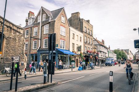 CAMBRIDGE, Reino Unido - 11 de agosto de 2015: Mujer joven en una bicicleta en una calle en Cambridge. Cambridge es una ciudad universitaria y una de las cinco mejores universidades del mundo.