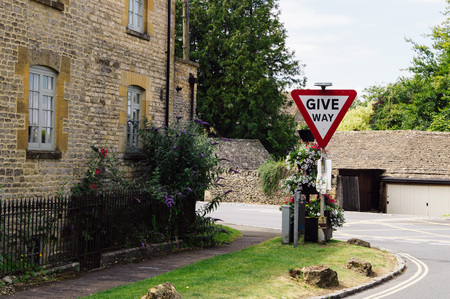stow: STOW ON THE WOLD, UK - AUGUST 12, 2015:  Give Way traffice signal decorated with flowers. Stow On The Wold is a delightful market town in the Cotswolds.