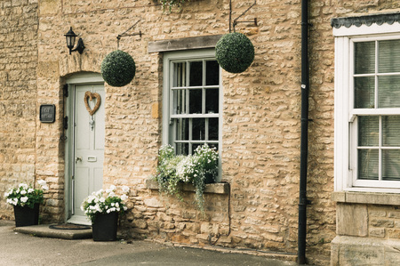 STOW-ON-THE-WOLD, UK - AUGUST 12, 2015:  Limestone cottage entrance decorated with flowers and natural elements.