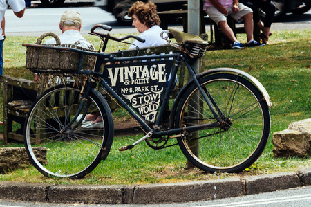 wold: STOW-ON-THE-WOLD, UK - AUGUST 12, 2015:  Old bicycle announcing an antique and vintage shop in Stow on the Wold. Stow on the Wold is a historical market town in the Cotswolds