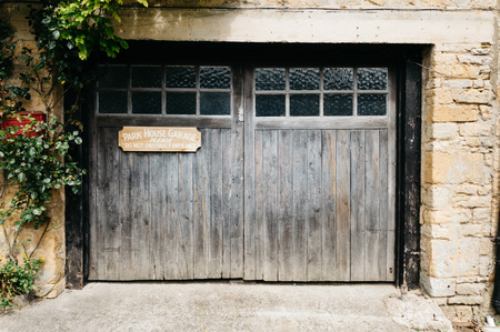 stow: STOW-ON-THE-WOLD, UK - AUGUST 12, 2015:  Park garage wooden door decorated with green  natural plants. Editorial