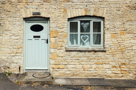 stow: STOW-ON-THE-WOLD, UK - AUGUST 12, 2015:  Limestone cottage entrance. Painted wooden  door and window.