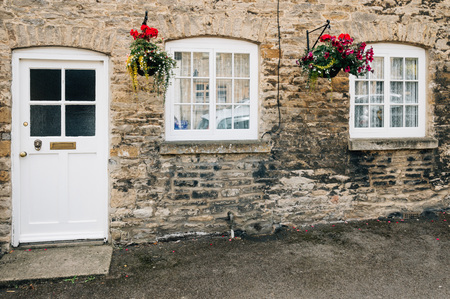 stow: STOW-ON-THE-WOLD, UK - AUGUST 12, 2015:  Limestone cottage entrance. Painted wooden  door and windows decorated with flowers and natural plants.