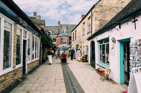 stow: STOW-ON-THE-WOLD, UK - AUGUST 12, 2015:  Commercial street with tourists in Stow on the Wold. Stow on the Wold is a historical market town in the Cotswolds