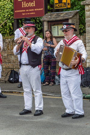 Stow on the Wold, UK - August 12, 2015: Morris Dancers dancing in a square at the village of Stow on the Wold in the Cotswolds, while some tourists are watching them.