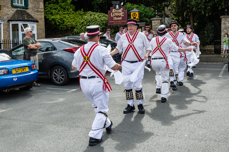 stow: Stow on the Wold, UK - August 12, 2015: Morris Dancers dancing in a square at the village of Stow on the Wold in the Cotswolds, while some tourists are watching them.