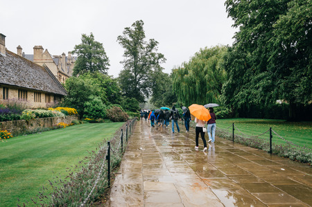 Outdoor view of the entrance to Christ Church College in Oxford a rainy day of summer and tourists with colorful umbrellas
