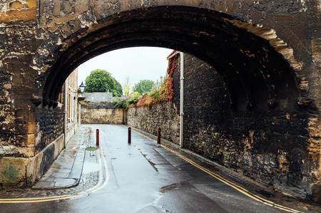 stone arch: Empty lane framed by an stone arch in Oxford a rainy day. The city is known as the home of the University of Oxford, the oldest university in the English speaking world. Editorial