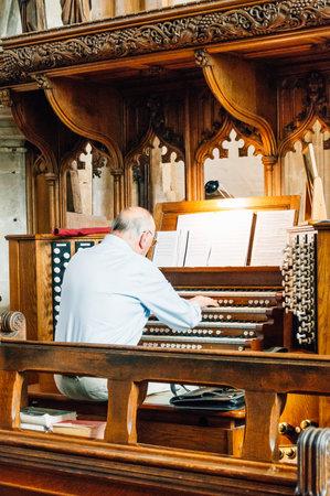 john the baptist: Cirencester, UK - August 17, 2015: Organist playing the organ in Parish Church of St John Baptist in Cirencester.