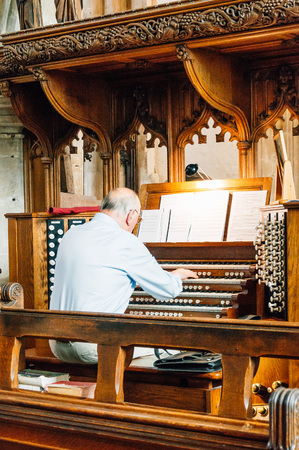 Cirencester, UK - August 17, 2015: Organist playing the organ in Parish Church of St John Baptist in Cirencester.