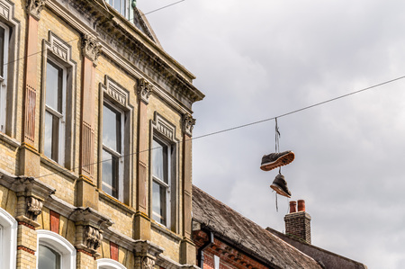 winchester: Sneakers hanging on powerlines against the buildings of the city of Winchester, UK