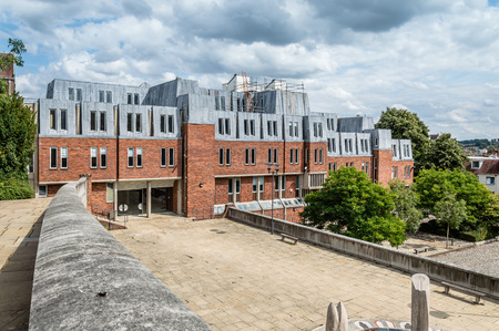 oficina antigua: Winchester, UK - August 16, 2015: Outdoors view of Modern office building in the center of the city a cloudy day.  Winchester is the ancient capital of England and former seat of King Alfred the Great.