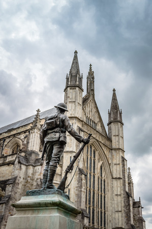 rifleman: Winchester, UK - August 16, 2015: Bronze statue of a rifleman against  Winchester Cathedral a cloudy day Editorial