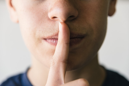 silence gesture: Boy doing a silence gesture Stock Photo