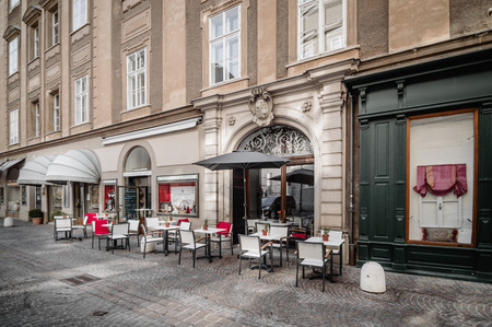 amadeus: Salzburg, Austria - April 29, 2015:  Terrace of cafe in the street. Salzburg is renowned for its baroque architecture and was the birthplace of Mozart. It is an Unesco World Heritage Site.