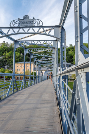 salzach: Salzburg, Austria - April 29, 2015: Mozarts bridge.  Old metal bridge over Salzach river. Salzburg was the birthplace of Mozart. It is an Unesco World Heritage Site. Editorial