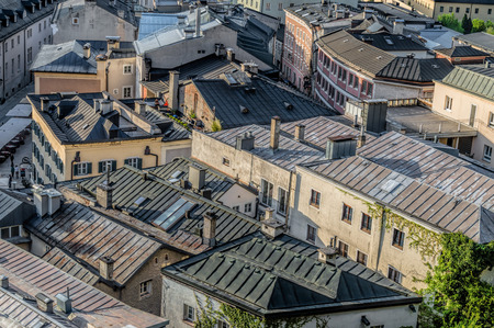 amadeus: Salzburg, Austria - April 29, 2015: Cityscape from the hill of Kapuzinerberg at dusk. Zinc roofs in residential buildings. Salzburg was the birthplace of Mozart. It is an Unesco World Heritage Site.