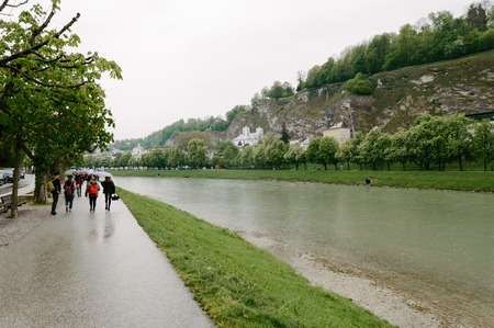 Salzburg, Austria - April 30, 2015:   Salzach river a rainy day. Salzburg is renowned for its baroque architecture and was the birthplace of Mozart. It is an Unesco World Heritage Site.