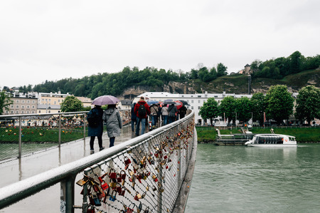 mozart: Salzburg, Austria - April 30, 2015:   Salzach river and bridge a rainy day. Salzburg is renowned for its baroque architecture and was the birthplace of Mozart. It is an Unesco World Heritage Site. Editorial