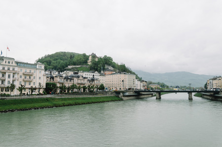 mozart: Salzburg, Austria - April 30, 2015:   Salzach river and bridge. Salzburg is renowned for its baroque architecture and was the birthplace of Mozart. It is an Unesco World Heritage Site.