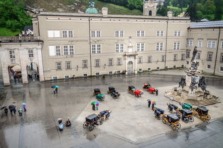 mozart: Salzburg, Austria - April 30, 2015: Horse driven carriages a rainy day. High angle view. Salzburg is renowned for its baroque architecture and was the birthplace of Mozart. It is an Unesco World Heritage Site.