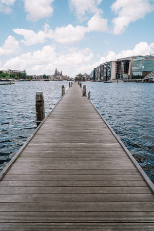 Amsterdam, Netherlands - August 1, 2016: Pesrspective of wooden jetty against amsterdam cityscape a cloudy day. Vertical composition Editorial